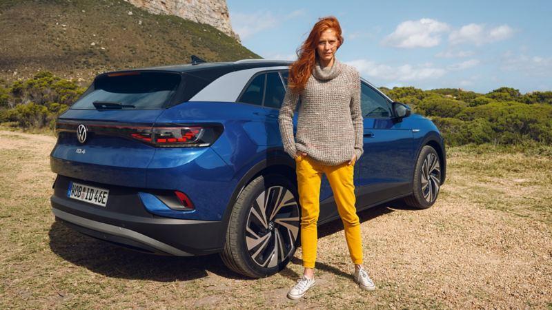 Une femme se tient debout à côté de l'ID.4 Volkswagen