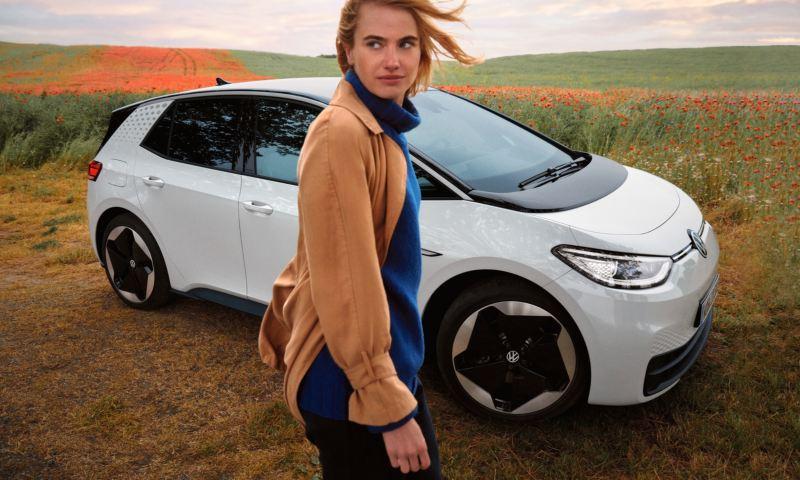 Una ragazza accanto a Volkswagen ID.3, vista lateralmente e parcheggiata in mezzo a un campo.