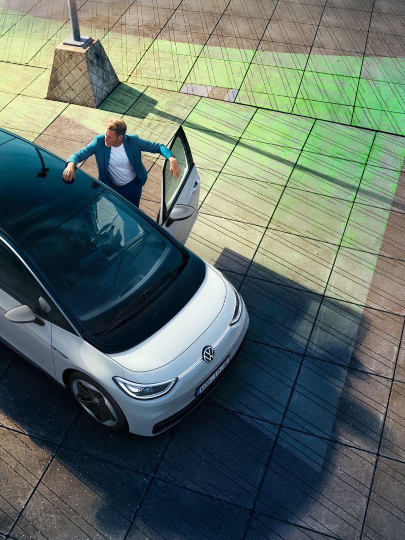 Mann im blauen Anzug steigt in den VW ID.3 ein