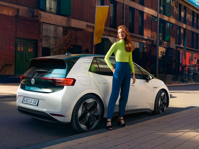 Woman in front of the white Volkswagen ID.3, view of the vehicle from the rear right