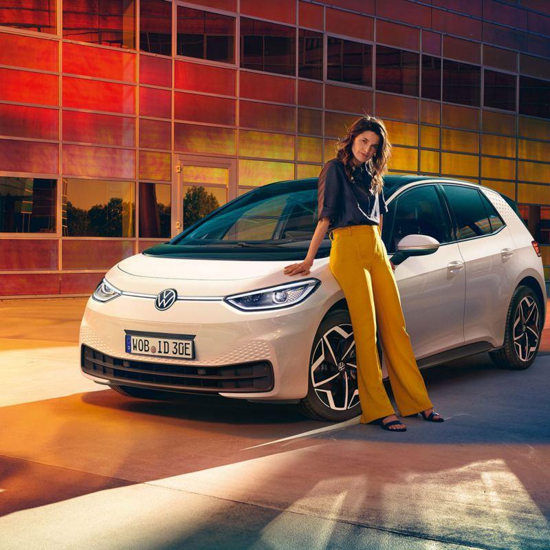 VW ID.3 in Weiß, Sicht auf Front mit Scheinwerfern und Felgen Andoya, Frau lehnt an Auto.