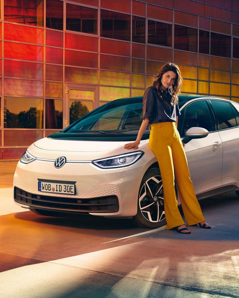 Eine junge, moderne Frau lehnt an einem weißen VW ID.3 in einem urbanen Setting.