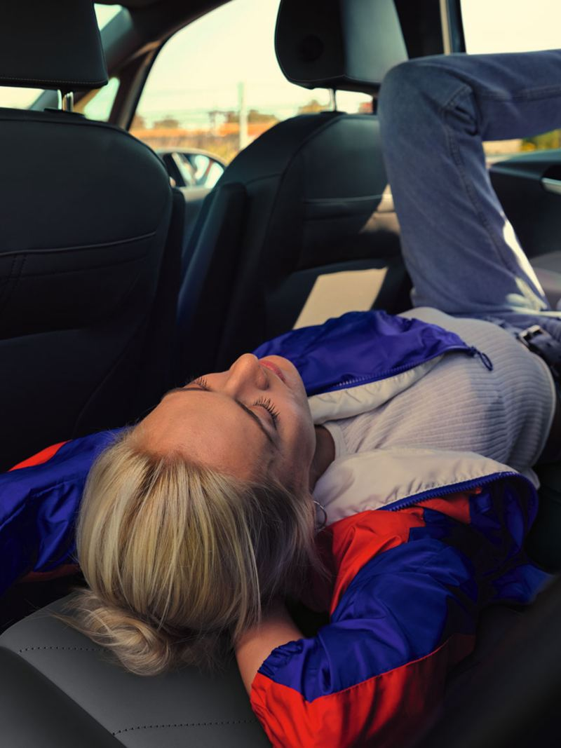 Junge Frau liegt auf der Rücksitzbank des VW ID3.