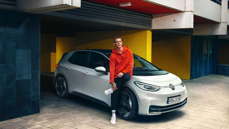 Ragazzo appoggiata a VW ID.3 parcheggiata in città