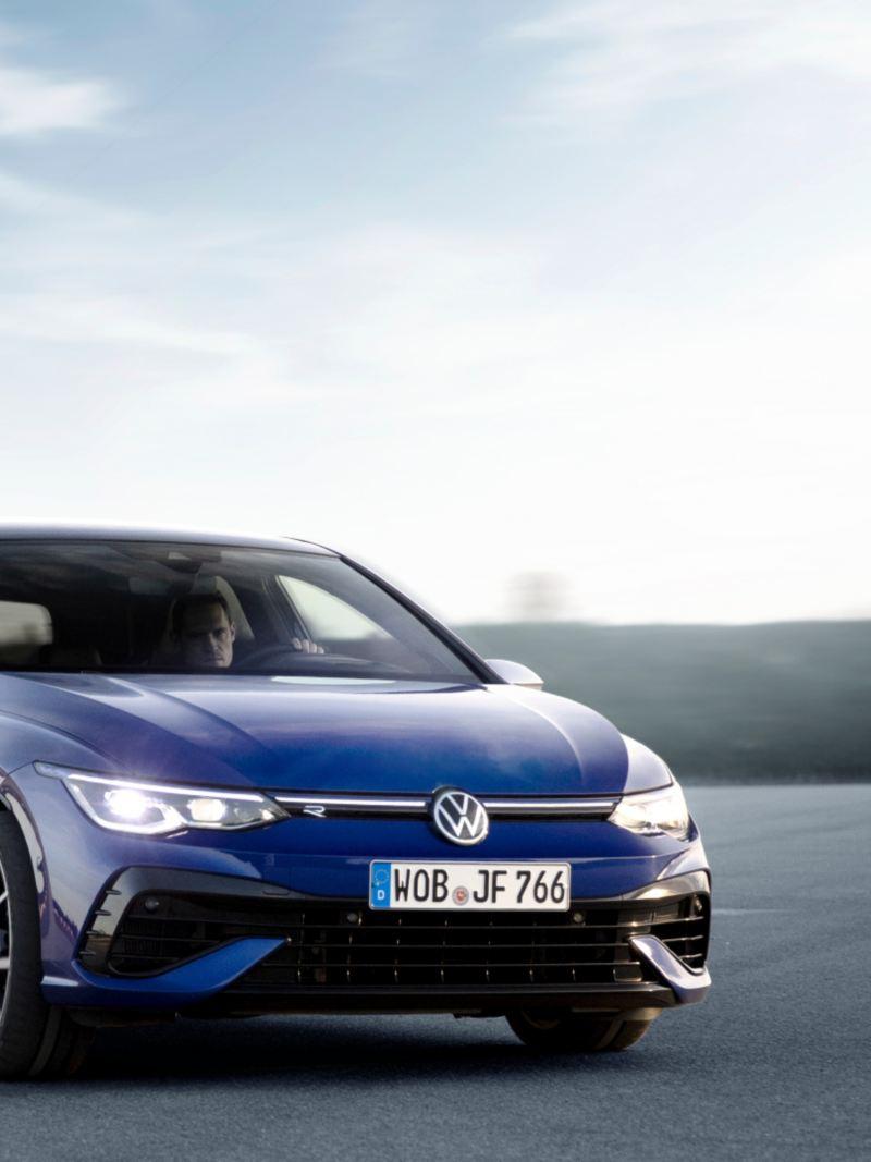 Nouvelle Volkswagen Golf-R 2022 de couleur bleue - Vue de face. Une voiture est garée sur l'asphalte gris.