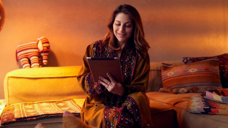 A woman browsing on a tablet at home