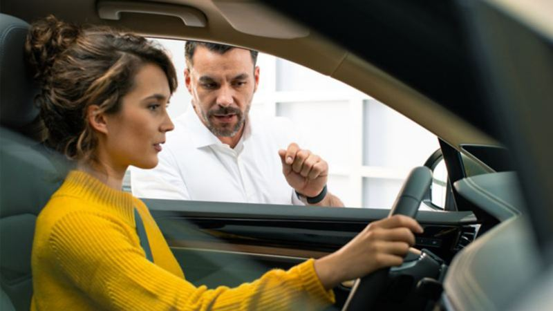 A woman sitting in the driver's seat while a car dealer speaks to her from outside the vehicle