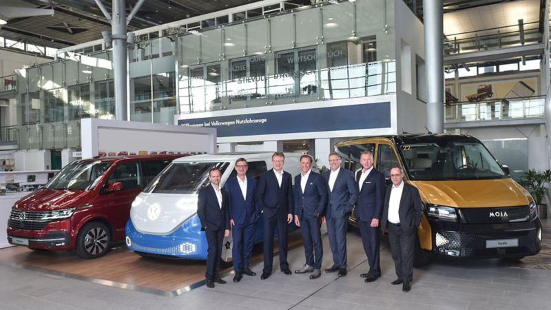 Thomas Sedran, Presidente del Consiglio di Amministrazione di Volkswagen Veicoli Commerciali, insieme ad altri uomini, in piedi davanti a tre veicoli commerciali VW.