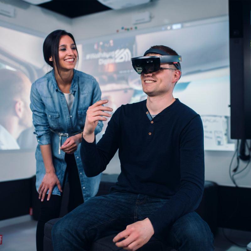 Ein junger Mann mit einer VR Brille und eine junge Frau, die neben im steht