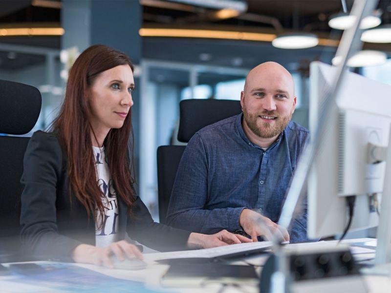 Eine Frau und ein Mann schauen gemeinsam auf einen Computerbildschirm