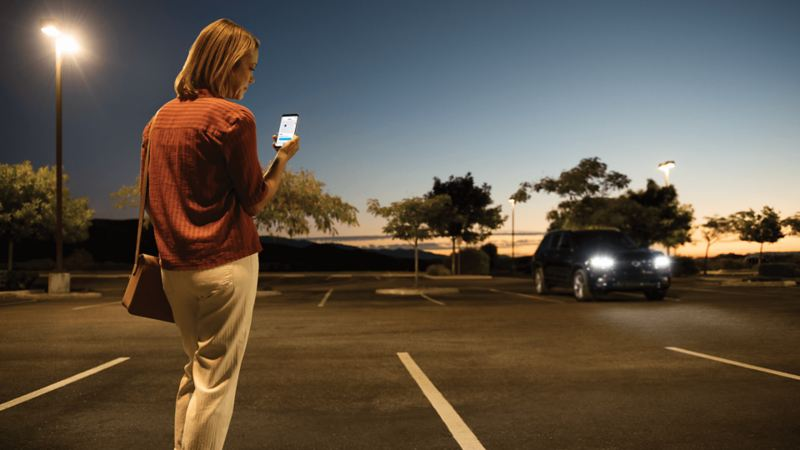 Woman in parking lot using the location services feature on the Car-Net® app