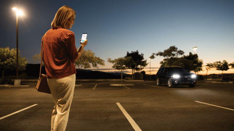 Une femme dans un stationnement utilisant la fonctionnalité de services de localisation sur l'application Car-NetMD
