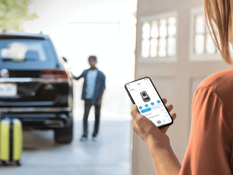 L'application Car-NetMD sur un téléphone avec un véhicule Volkswagen en arrière-plan