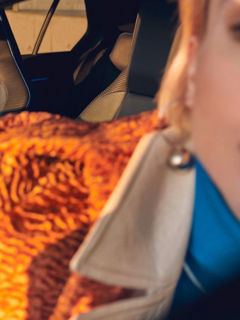 Una donna siede a bordo della sua Volkswagen Golf R – interni sportivi