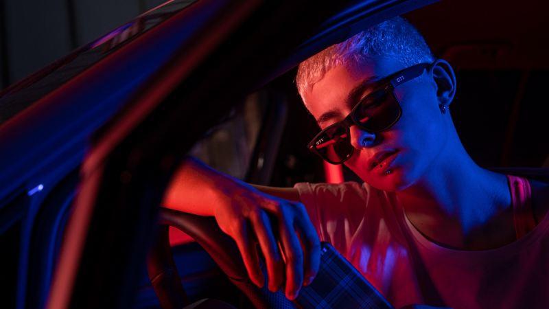 Une jeune femme en tenue GTI assise dans sa VW
