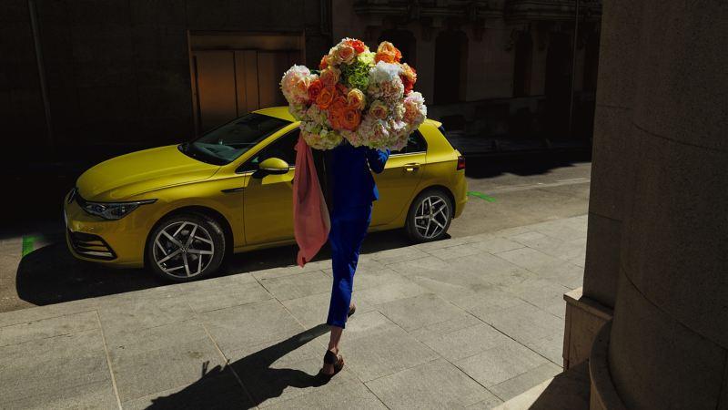 Une femme habillée en bleu portant un grand bouquet de fleurs se dirige vers une VW Golf 8