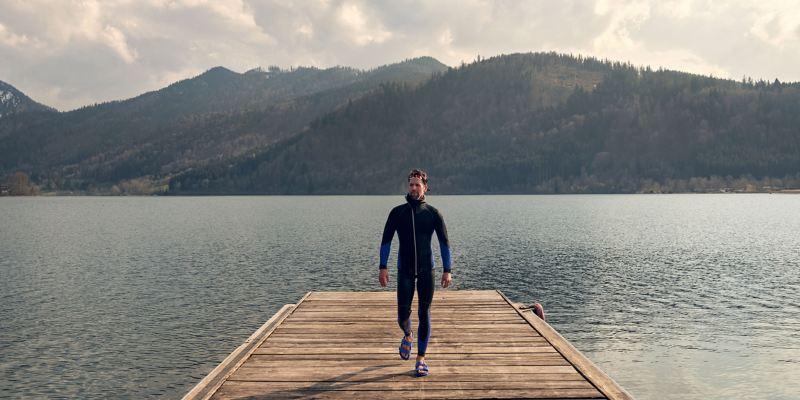Un uomo su un sentiero, dietro di lui un panorama di montagna