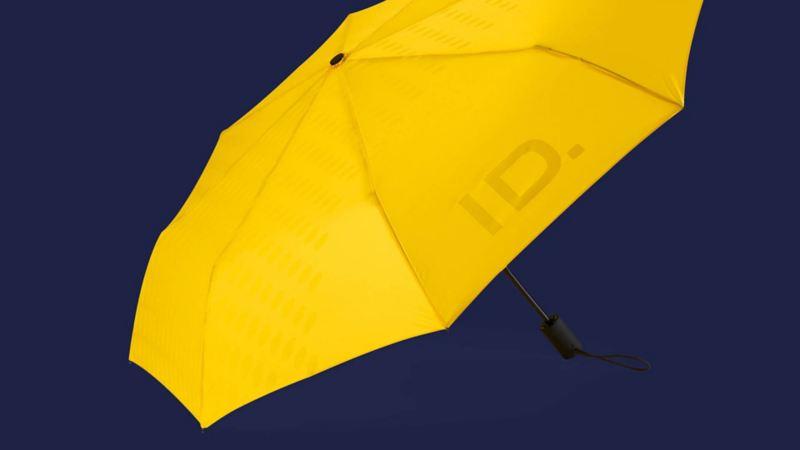 Un ombrello tascabile giallo originale Volkswagen, con logo ID. sulla superficie e sull'impugnatura.