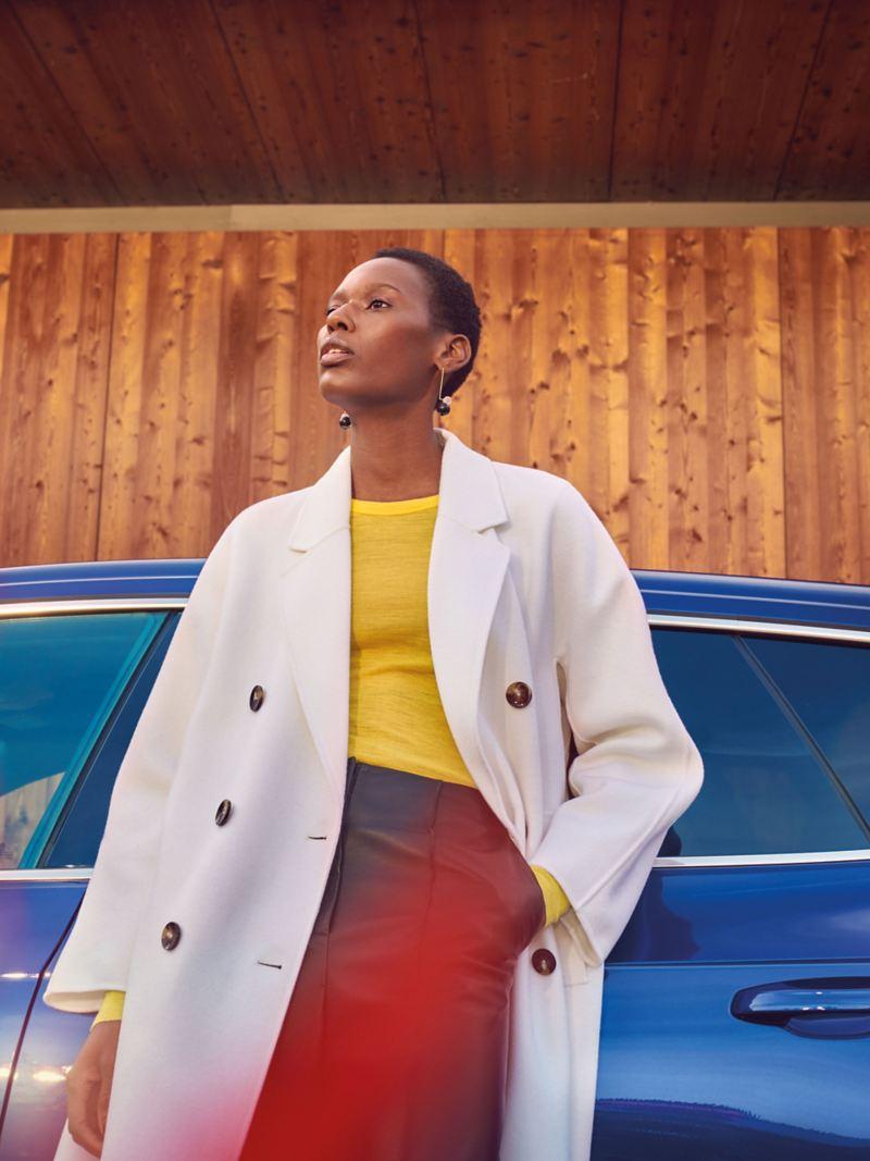 Une femme est appuyée sur sa VW Arteon R Shooting Brake