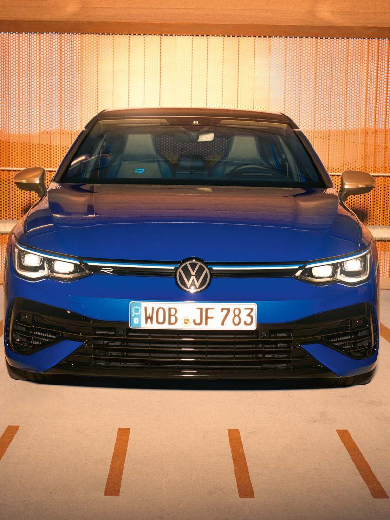 Una donna è in piedi accanto alla sua Volkswagen Golf R posteggiata