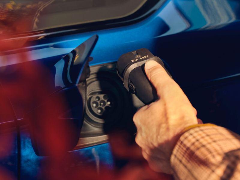 Un autista inserisce il cavo di ricarica - VW Touareg R eHybrid
