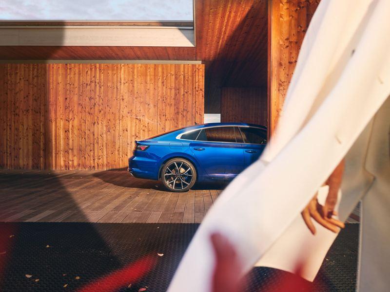 A blue VW R Arteon R stands under a carport
