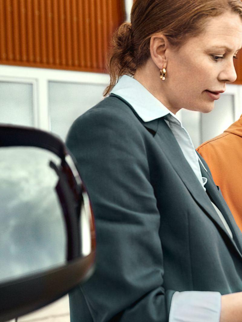 Zwei Personen stehen neben einem VW Transporter und blicken auf ein Tablet.
