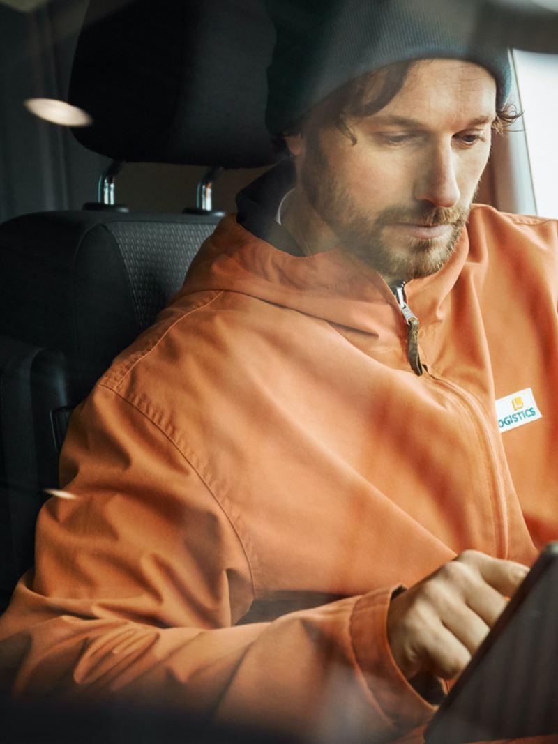Ein Mann sitzt in einem VW Transporter und bedient ein Tablet.