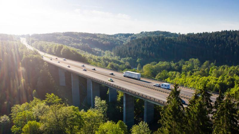 Cars and trucks drive over a bridge