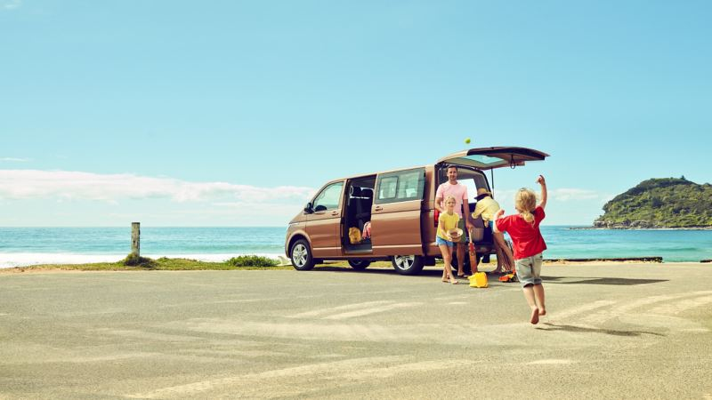 Family unloading Volkswagen Multivan parked by a beach front.