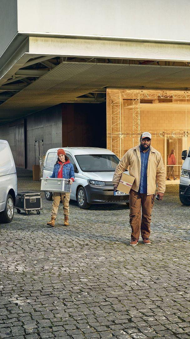 Tre operai scaricano alcuni pacchi dai loro veicoli commerciali Volkswagen