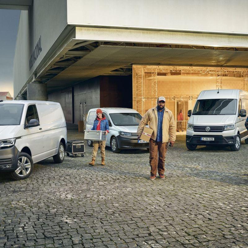 Tre operai scaricano alcuni pacchi dai loro veicoli commerciali Volkswagen; Transporter Furgone, Amarok, Nuovo Caddy Cargo e Crafter Furgone.