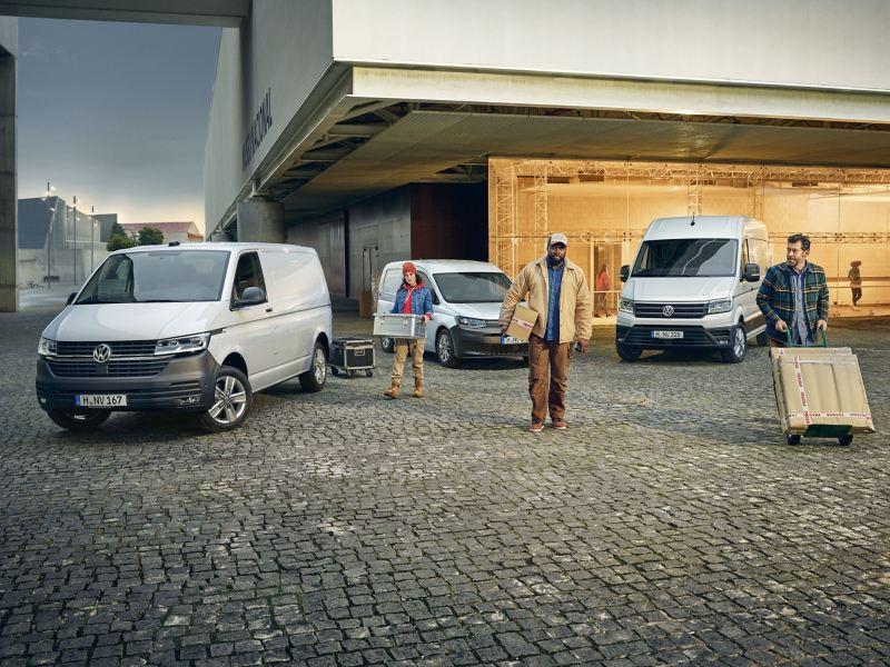 Tre lavoratori si allontanano dai loro veicoli commerciali Volkswagen, parcheggiati davanti a un magazzino.