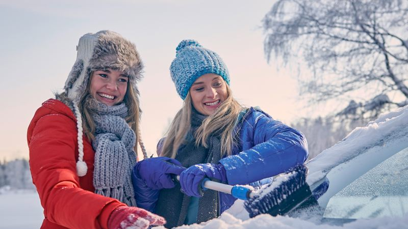 """Two girls are cleaning a car's window in snow, link out to VW' """"newcomer program"""" page"""