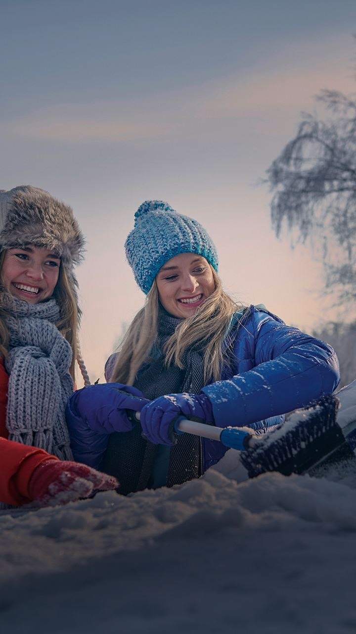 Two girls are cleaning a car's window in  snow