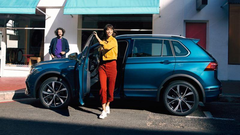 Ragazza esce dalla portiera del guidatore di Volkswagen Nuova Tiguan.