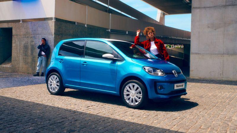 Volkswagen up! parcheggiata su una strada acciottolata due ragazzi giovani aspettano