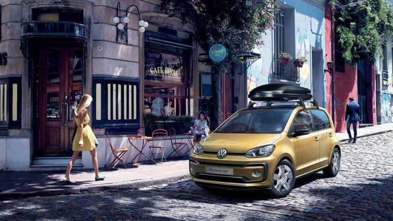 """Vista 3/4 frontale di Volkswagen Nuova up! parcheggiata davanti a un bar. Sul tettuccio il box da viaggio """"Comfort"""" originale Volkswagen."""