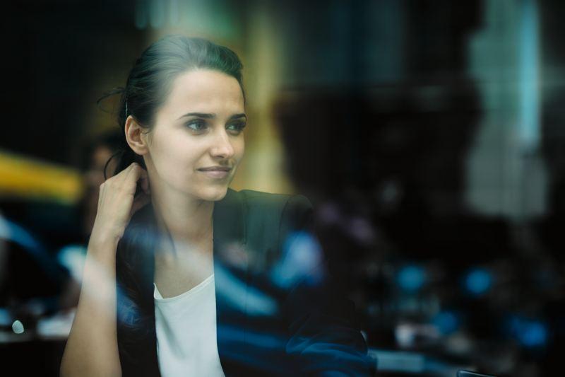 Donna in ufficio, fotografata attraverso una vetrina.