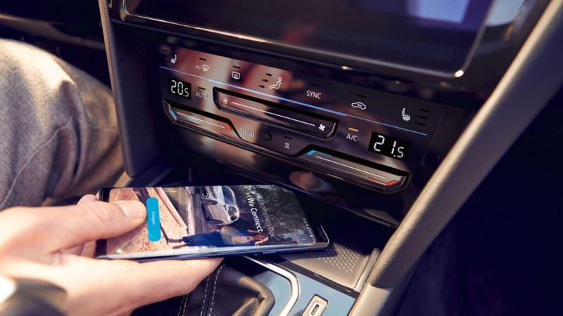 Interface téléphonique Comfort de la Passat, une main pose un smartphone dans le compartiment afin de le recharger par induction, la page d'accueil de We Connect est visible sur l'écran du smartphone.