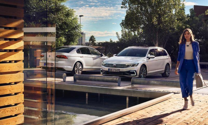 Πίσω όψη του νέου Volkswagen Passat GTE και μπροστινή όψη του νέου Volkswagen Passat GTE Variant το ένα δίπλα στο άλλο σε χώρο στάθμευσης, γυναίκα επιχειρηματίας περπατά από τον χώρο στάθμευσης προς ένα κτίριο