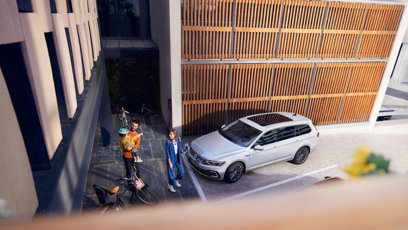 VW Passat GTE Variant, vista dall'esterno in diagonale dall'alto in un parcheggio davanti a una parete di legno, una famiglia sul marciapiede