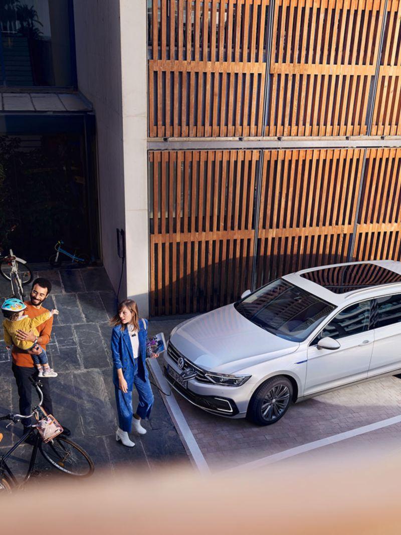 Passat GTE Variant kuvattuna yläviistosta pysäköitynä talon parkkiruutuun. Auton edessä on nuori perhe