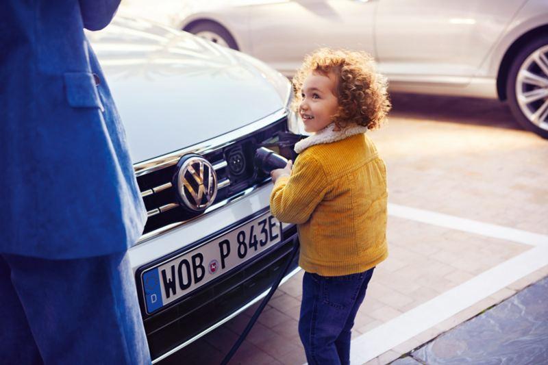 Detailansicht der Ladevorrichtung eines weißen VW Passat GTE am Kühlergrill. Kind hält lächelnd den Ladestecker in die Vorrichtung.