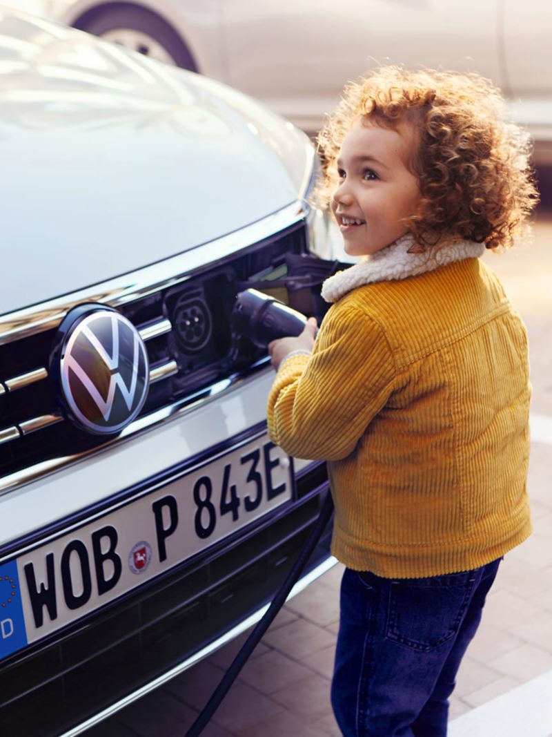 VW Passat GTE front, charging process, child pulls charging nozzle out of car