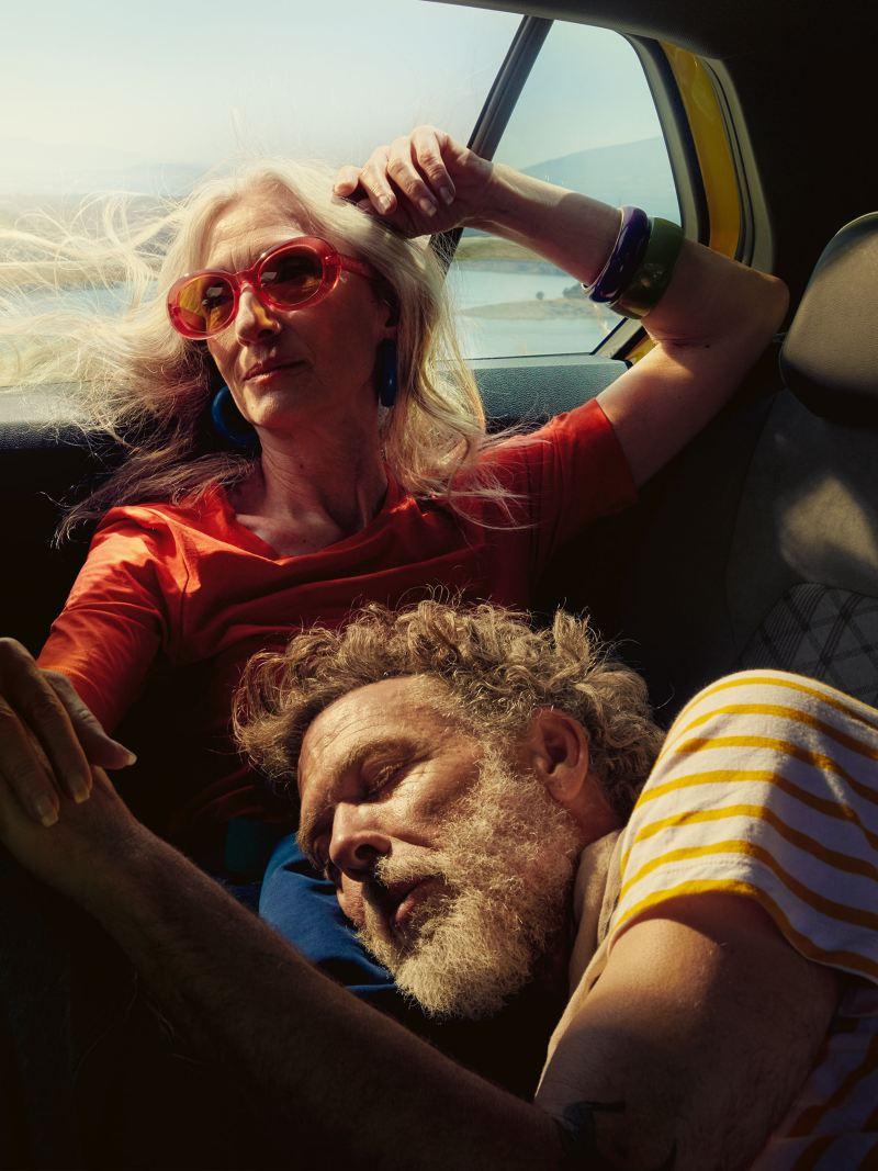 Un uomo e una donna sui sedili posteriori di un'auto Volkswagen.