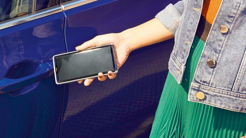 VW Passat, buitenaanzicht, mobiele sleutel. Vrouw opent de auto met de smartphone