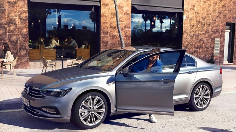 """Passat limousine Elegance in pyrite-silver with wheel """"Verona"""", side-front standing, man gets out of the car"""