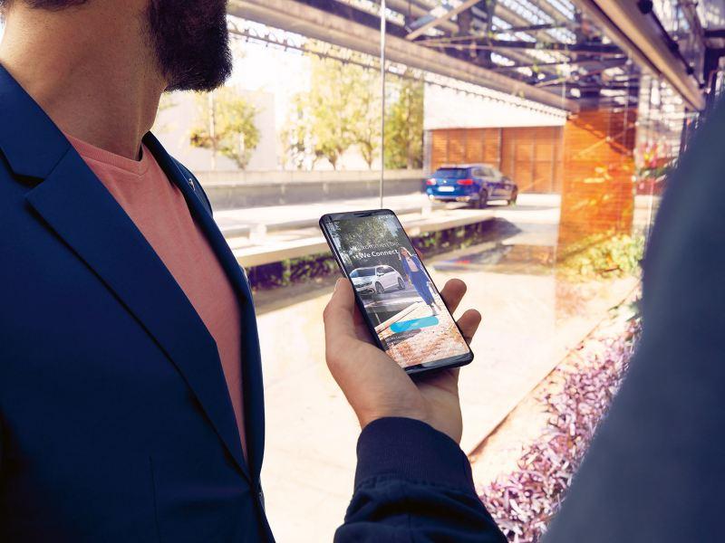 Un uomo tiene in mano il proprio smartphone con la schermata dell'app We Connect di Volkswagen. Fuori da una vetrata una Passat Variant in versione 'R-Line'.