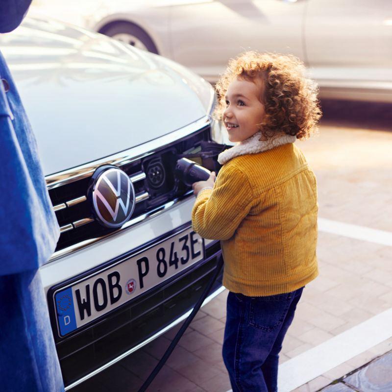 bambina inserisce connettore nella spina frontale auto VW ibrida plug in